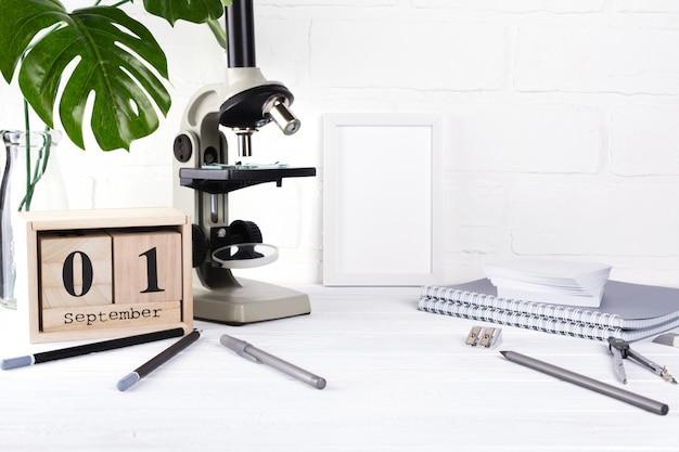 Группа школьных принадлежностей, микроскоп и деревянный календарь