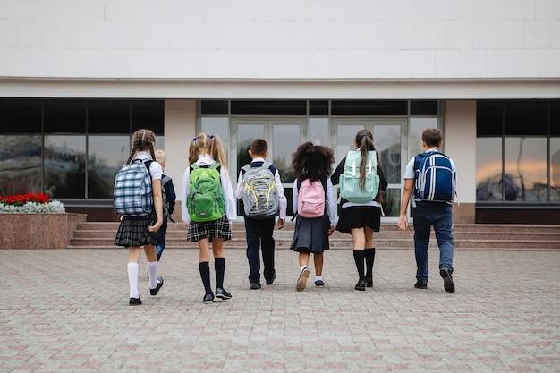 다채로운 배낭과 제복을 입은 학생 그룹이 학교 앞에 줄을 서 있습니다. 다시보기.