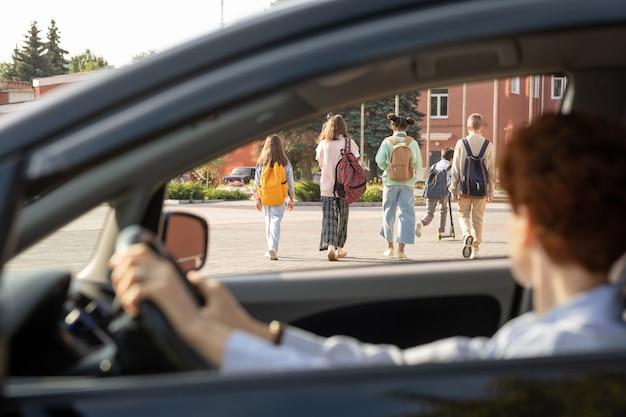 Группа школьников, движущихся по улице, в то время как молодая женщина в машине смотрит на них