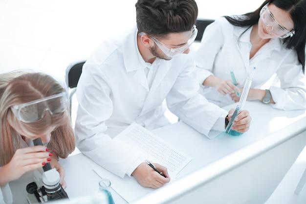 과학자 그룹이 연구를 수행하고 저널에 항목을 작성합니다.