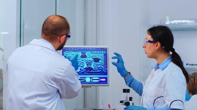 コンピューターのデスクトップを指している近代的な設備の整った実験室で働いている科学者のグループ。 covid19ウイルスに対するハイテク研究診断を使用してワクチンの進化を調べる医師のチーム