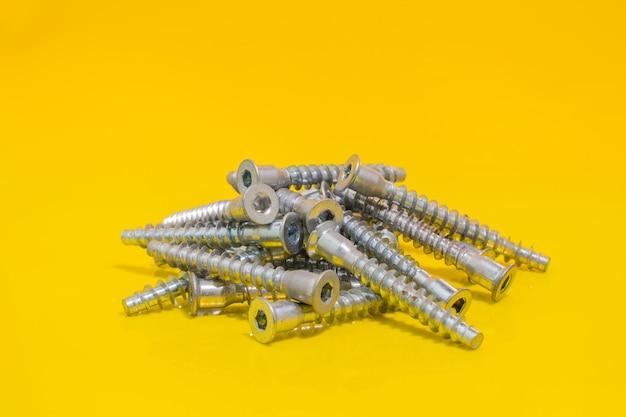 노란색 배경에 조립하는 가구용 나사 볼트 그룹입니다. 재고 사진.