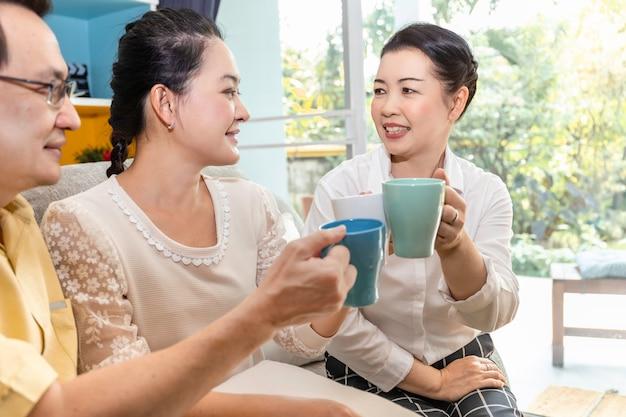 Группа в составе старшая азиатская выбытая встреча друга и выпивая кофе в доме престарелых.