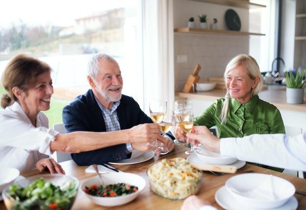 Группа старших друзей, наслаждаясь званым ужином дома, чокаясь.