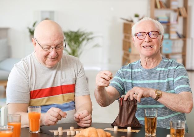 Группа пожилых людей, проводящих время вместе в доме престарелых