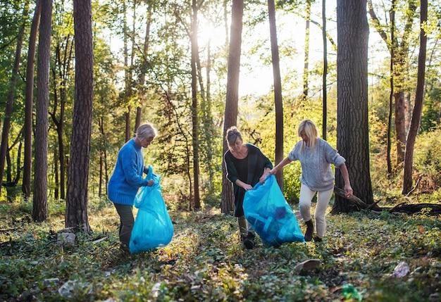 森の中で屋外でゴミを拾う年配の女性の友人のグループ、目録の概念。