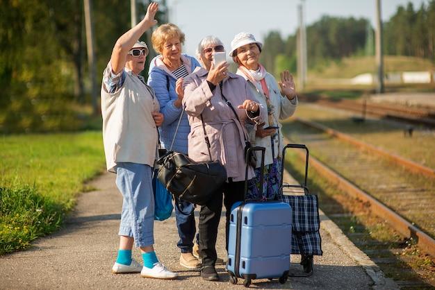 노인 여성 그룹이 기차 여행을 기다리는 플랫폼에서 자화상을 찍습니다.