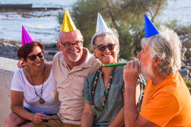 パーティーの帽子をかぶってビーチに座って男を見て笑っている高齢者と成熟した人々のグループ-パーティーや誕生日のコンセプト