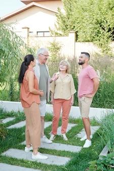 夏の日に裏庭で一緒に立って何かについておしゃべりする高齢者と若い大人のグループ、フルショット