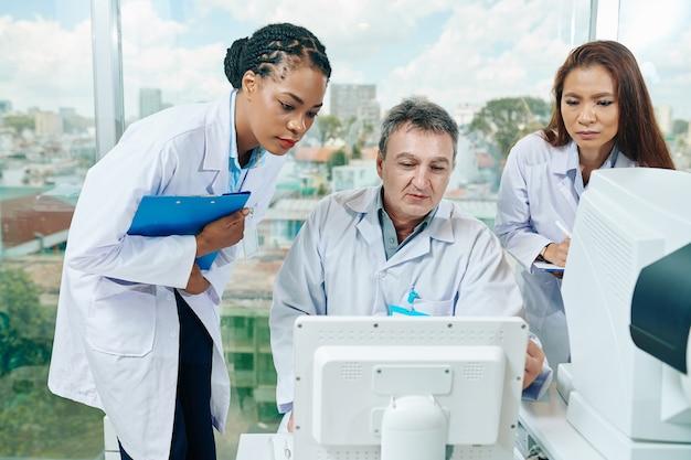 컴퓨터 화면에서 건강 검진 결과를 논의하는 심각한 안과 의사 그룹