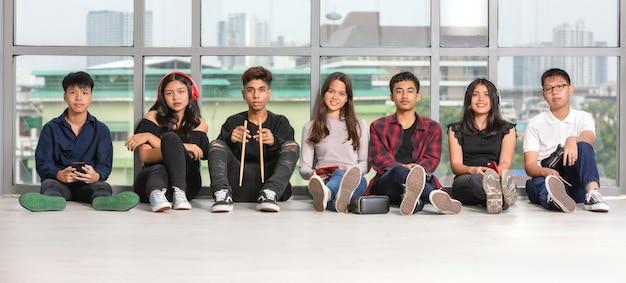 Группа из семи дружелюбных молодых мужчин и женщин-подростков с милой улыбкой, сидя на полу и глядя в камеру. сидят юные музыканты. понятие отношения друзей колледжа