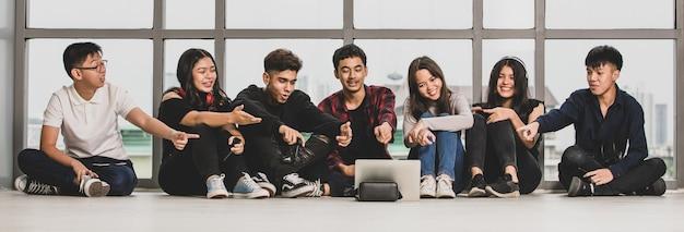 캐주얼 옷을 입은 7명의 젊은 남성과 여성 10대 그룹이 바닥에 앉아서 태블릿을 손가락으로 가리키고 있습니다. 대화를 나누기 위해 친구와 온라인으로 화상 통화를 하는 대학생