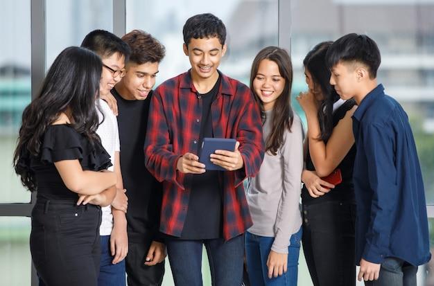 Группа из семи молодых мужчин и женщин-подростков в повседневной одежде, стоя и глядя на экран планшета с привлекательной улыбкой. студент колледжа с помощью планшета для видеосвязи онлайн с друзьями