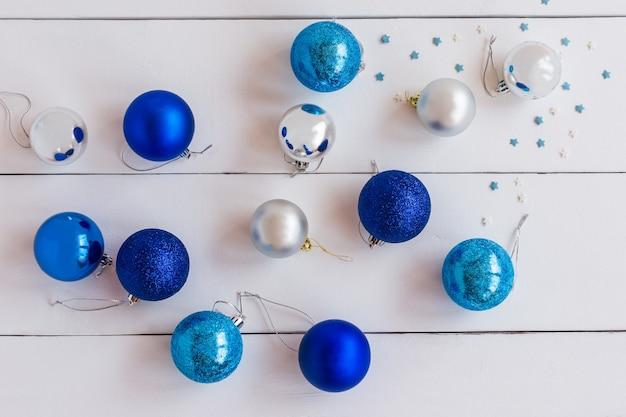 Группа блестящих елочных шаров синего и серебристого цветов на деревянных фоне.