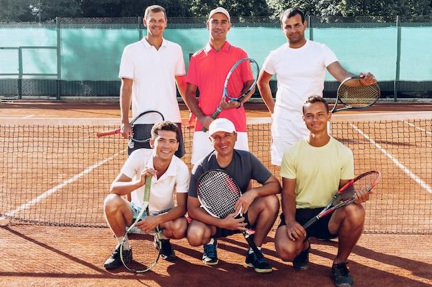 Группа из шести теннисистов-мужчин, стоящих на корте