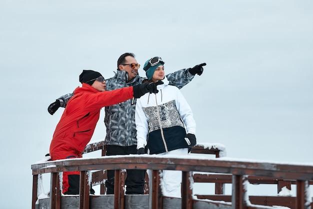 산에있는 스키어 친구 그룹은 스키 리프트의 배경에 보온병에서 쉬고 커피를 마시고 있습니다.