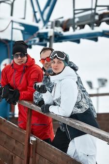 산에있는 스키어 친구 그룹은 스키 리프트의 배경에 보온병에서 커피를 마시고 쉬고 있습니다.