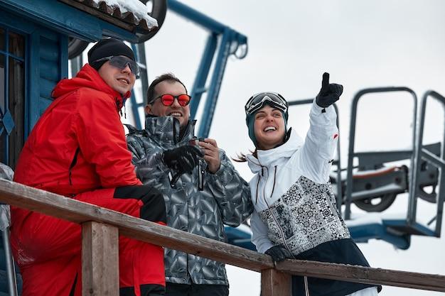 山のスキーヤーの友人のグループは、スキーリフトの背景にある魔法瓶から休んでコーヒーを飲んでいます。