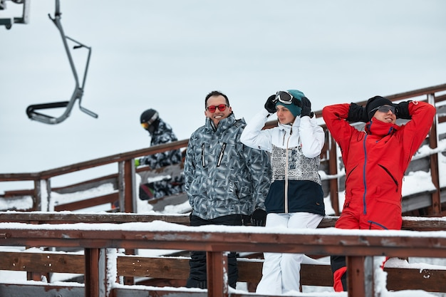 산에있는 스키어 친구 그룹은 스키 리프트 표면의 보온병에서 쉬고 커피를 마시고 있습니다.