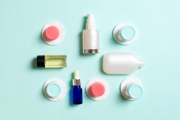 Группа маленьких бутылочек для путешествий на цветном фоне. скопируйте место для своих идей. плоская композиция косметических продуктов. вид сверху кремовых контейнеров с ватными дисками.
