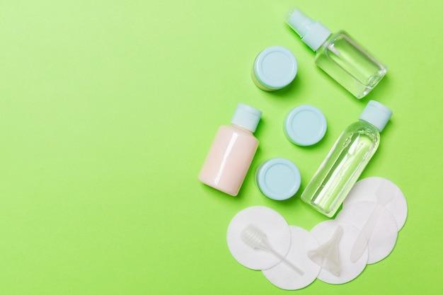 Группа маленьких бутылочек для путешествий на зеленом фоне. скопируйте место для своих идей. плоская композиция косметических продуктов. вид сверху кремовых контейнеров с ватными дисками.