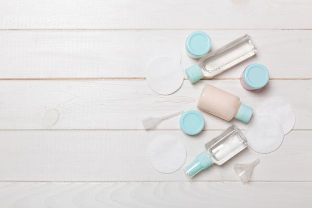 Группа маленьких бутылочек для путешествий на деревянных фоне. скопируйте место для своих идей. плоская композиция косметических продуктов. вид сверху кремовых контейнеров с ватными дисками.