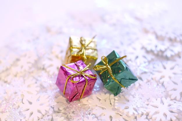 白い人工雪片の背景に小さな明るくカラフルなギフトボックスのグループ。クリスマスと新年の装飾。