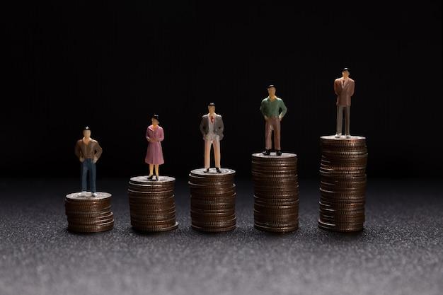 동전에 서있는 작은 실업가의 그룹