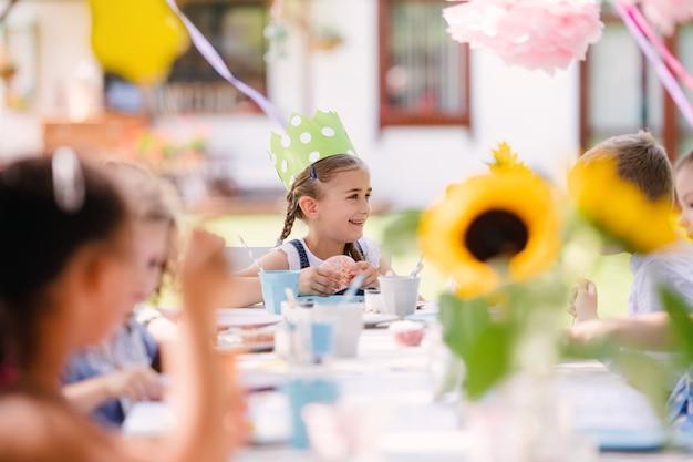 夏のガーデンパーティーで屋外のテーブルに座って、食べている小さな子供たちのグループ。