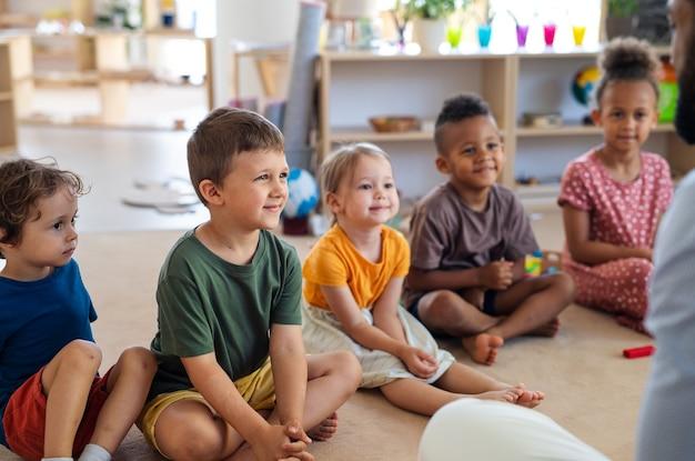 교실에서 실내 바닥에 앉아 있는 작은 보육원 아이들의 그룹.