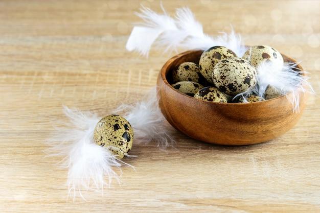 그릇에 흰 깃털을 가진 작은 발견 메 추 라 기 계란의 그룹