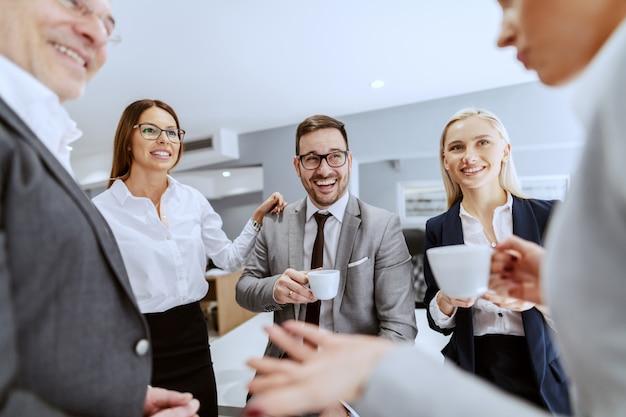 陽気な同僚が座っていると職場に立って、チャットや一時停止でコーヒーを飲みながら笑顔のグループ。