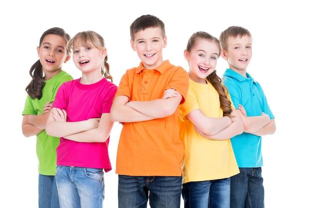 Группа улыбающихся детей со скрещенными руками в красочных футболках, стоящих вместе на белом фоне.