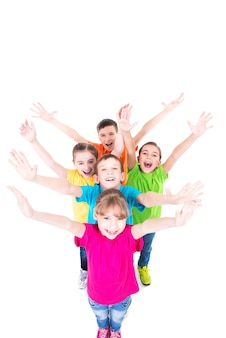 Группа улыбающихся детей с поднятыми руками в красочных футболках, стоя вместе. вид сверху. изолированные на белом.