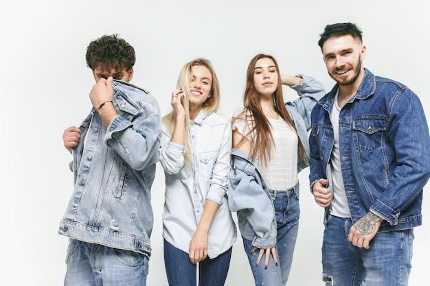 ファッショナブルなジーンズで笑顔の友達のグループ。スタジオでポーズをとる若い男性と女性。ファッション、人々、幸せ、ライフスタイル、服のコンセプト