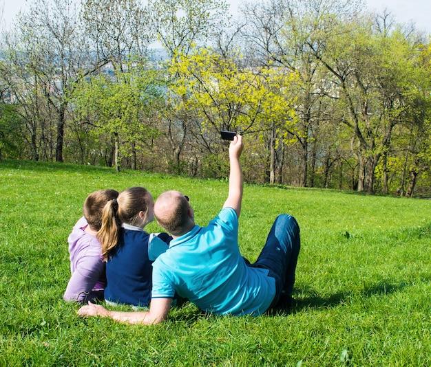 芝生の上に座って公園で自分撮りをしているスマートフォンで笑顔の友達のグループ