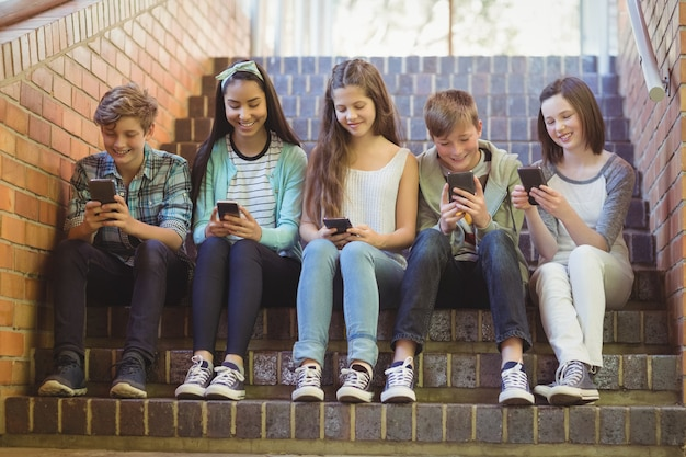 携帯電話を使用して階段に座っている笑顔の学校の友達のグループ