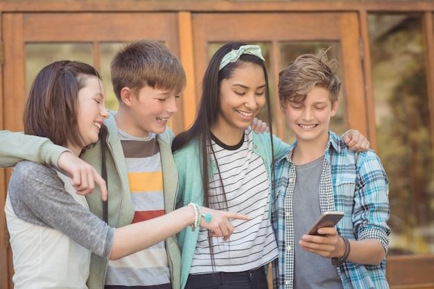 携帯電話を使用して笑顔の学校の友達のグループ