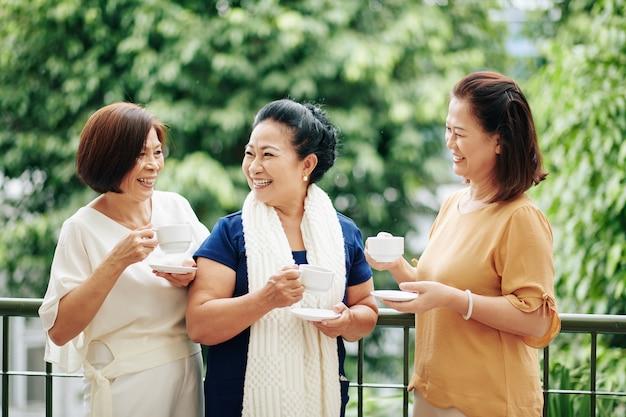 큰 현관에 서 있을 때 차를 마시고 뉴스를 토론하는 웃는 고위 여자 친구 그룹