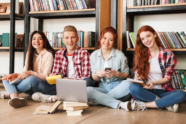 宿題をしている笑顔のティーンエイジャーのグループ