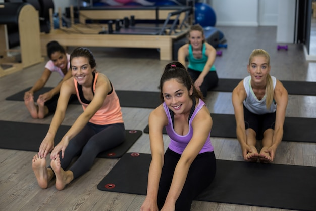 Группа улыбающихся женщин, выполняющих упражнения на растяжку