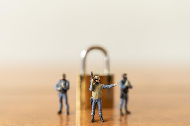 Группа солдат или полицейская миниатюрная фигура с пулеметом, стоящая с золотым замком-ключом