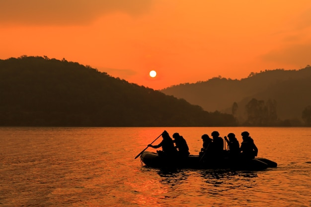 군인 그룹은 황혼, 산 및 태양을 배경으로 목표로 보트를 노를 저어주는 것을 돕습니다.