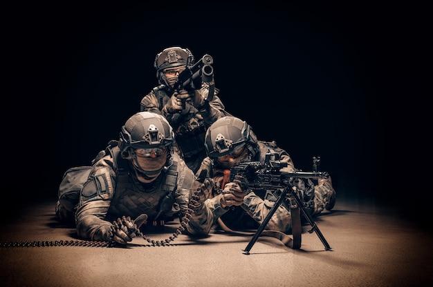 군복을 입은 군인 그룹이 총격을 가하고 있습니다. 무거운 기관총, 유탄 발사기.