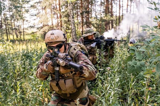 군사 정찰 작업을 수행하는 동안 숲 덤불을 통해 이동하는 제복을 입은 군인 그룹