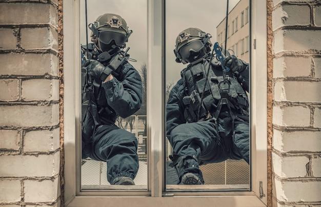특수 부대 전투기 그룹은 창문을 통해 건물을 습격합니다. 혼합 매체