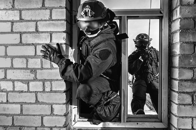 特殊部隊の戦闘機のグループが窓から建物を襲撃します