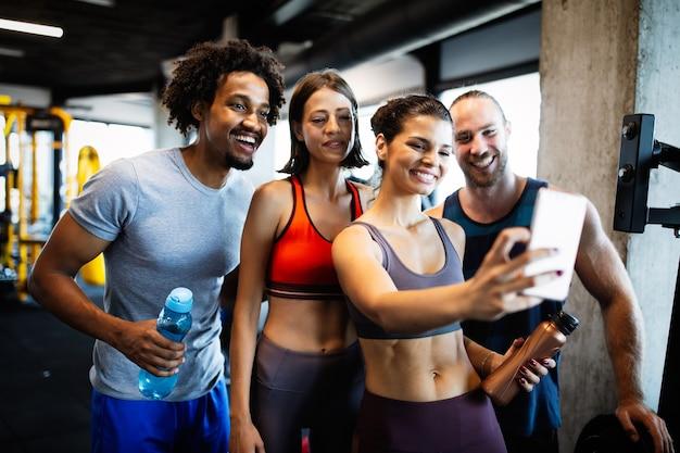 自撮りをしているジムのスポーティーなフィットの人々のグループ。フィットネスクラブのライフスタイルとスポーツに関する概念