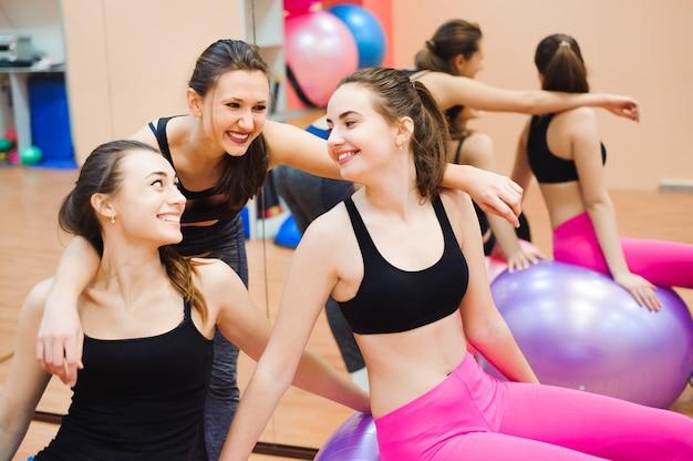 ジムでスポーツの人々のグループ-トレーニング中にウエイトルームでハッピースポーティーな友達-ライフスタイルとフィットネスクラブでのスポーツについての概念。
