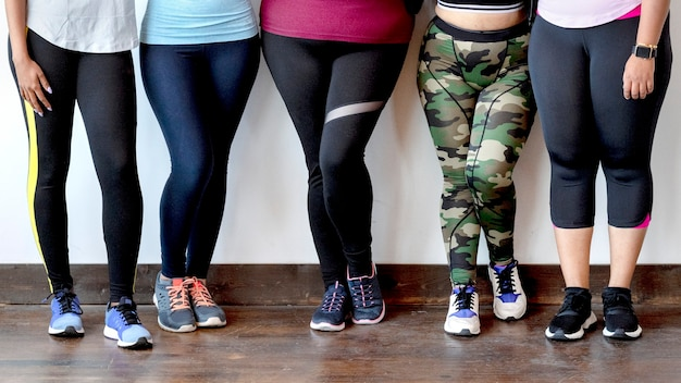 レンガの壁のそばに立っているスポーツ女性のグループ